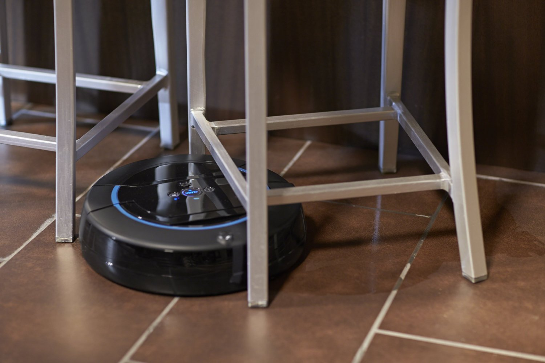 моющий робот-пылесос IROBOT Scooba 450 маневрирует между ножками стульев