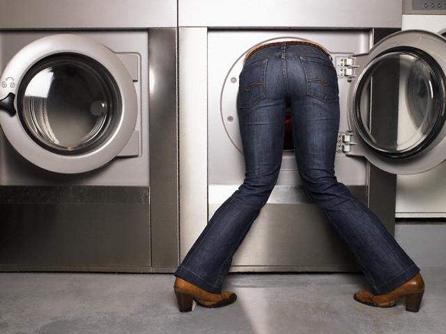 женщина в стиральной машине, голова в стиральной машине, достает белье из барабана стиральной машины