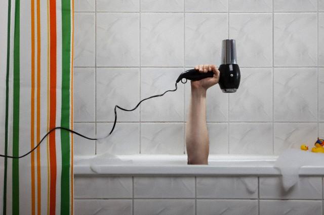 из ванной торчит рука, которая держит фен