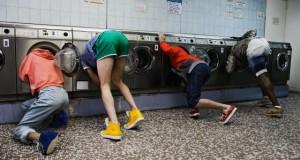 четыре человека, которые засунули головы в стиральную машины