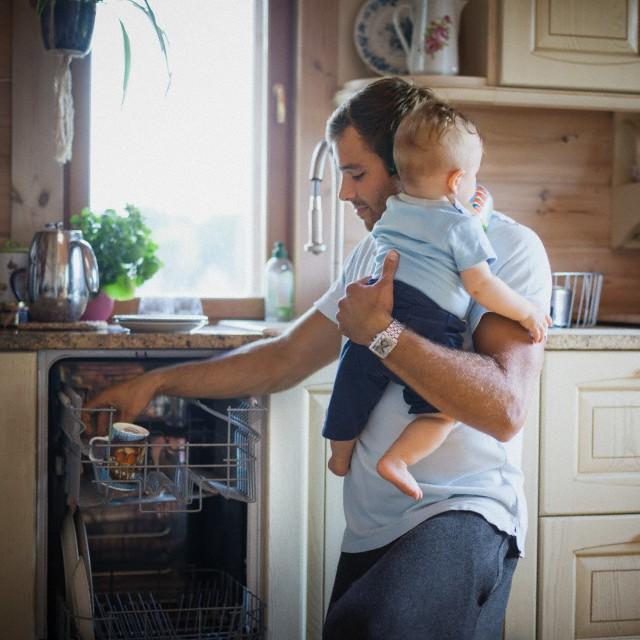 мужчина с реенком на руках моет посуду в посудомоечной машине