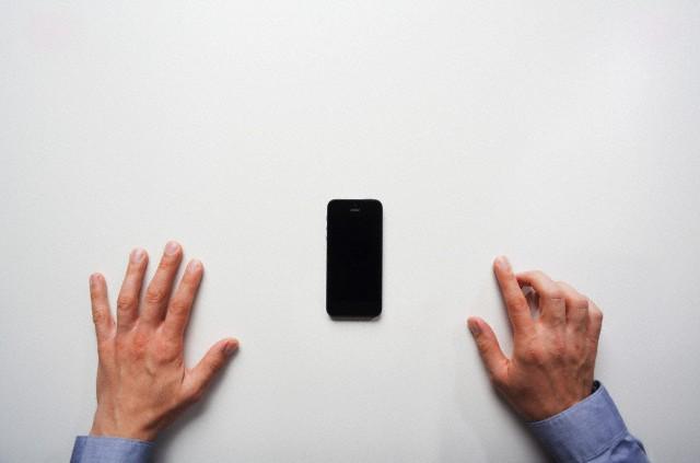 бизнесмен готовится позвонить по телефону, руки на столе, бизнесмен берет телефон