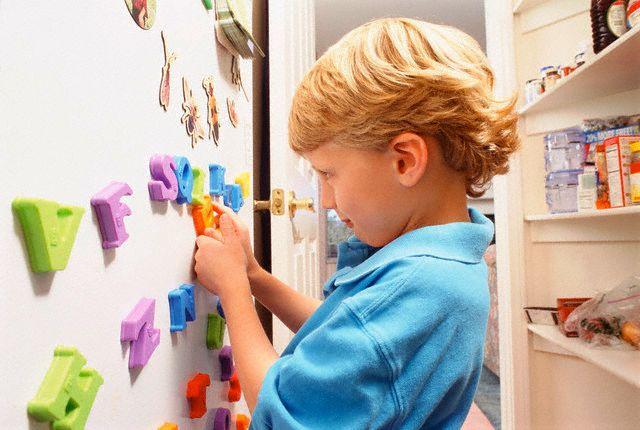 ребенок играется с магнитом на холодильнике